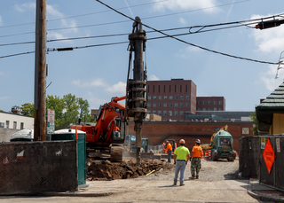 Construction crews watch as a machinery drills into the ground along South Crouse Avenue. Photo taken July 18, 2017